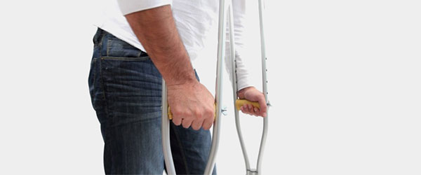 Man with crutches suffering from a long-term disability